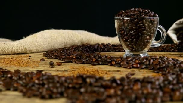 Path made with coffee beans on wooden table, cup and bag with coffee beans on background, dolly