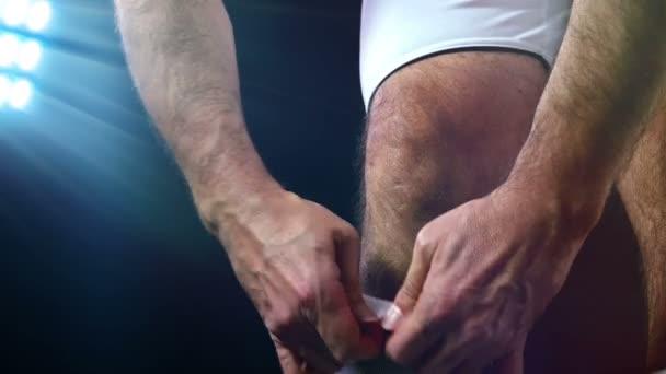 Fotbal, fotbalové hry. Profesionální fotbalista úpravu jeho ponožky, černé pozadí