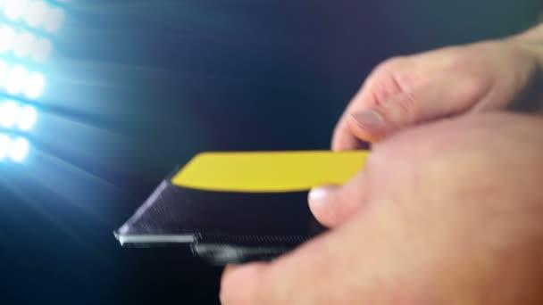 Labdarúgás / Foci játékvezető mutatja büntetés sárga kártya fekete háttér