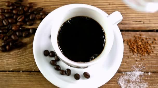Zpomalený pohyb nalévání mléka do šálku kávy na starý dřevěný stůl, pohled shora