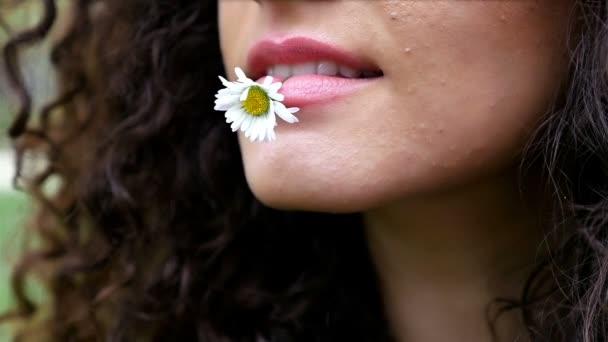 Portré egy csinos, fiatal nő, gyönyörű göndör haja a százszorszép szájban, lassított