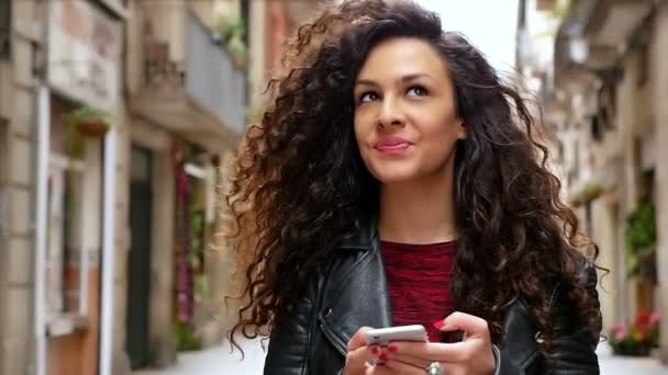 Portrait of young woman with smart phone walking in the city streets, slow motion
