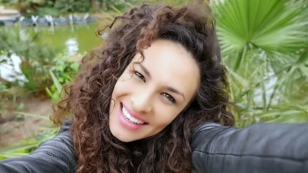 Portrait of happy young woman with beautiful curly hair taking selfie in the park, slow motion