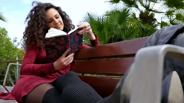 Mladá žena s krásnými kudrnatými vlasy čtení knihy na lavičce v parku, zpomalení