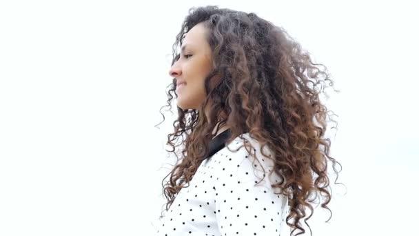 Portré boldog fiatal nő, gyönyörű göndör haja fehér háttér, lassú mozgás