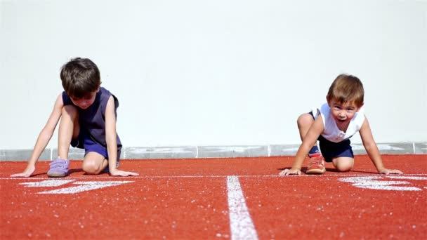 Vtipné video s dvěma malými kluky Příprava ke spuštění v atletické dráhy
