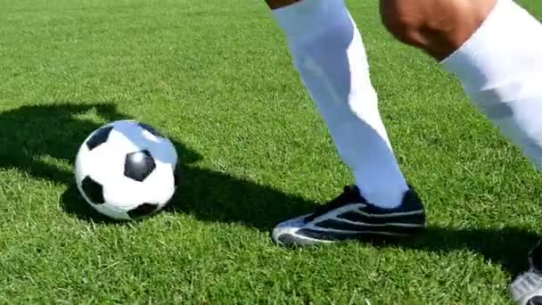 Fußballer führt den Ball auf einem Fußballplatz, Zeitlupe