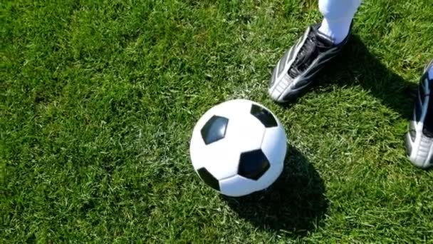 Soccer ball on the center point of a football field, player kicking the ball