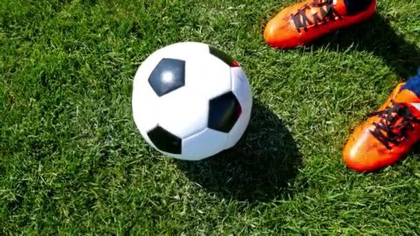 Fußball auf dem Mittelpunkt eines Fußballfeldes, Spieler kickt den Ball