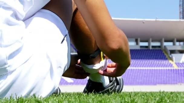 Fotbalista v bílém oblečení úprava jeho ponožky na hřišti