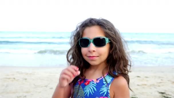 Nettes kleines Mädchen flirtet mit Sonnenbrille am Strand