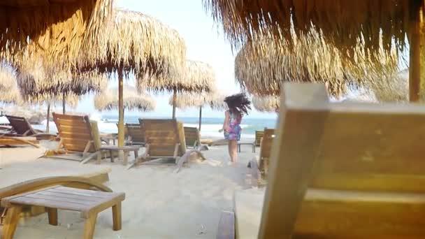 Nettes kleines Mädchen läuft auf Strohschirmen und hölzernen Meeresböden am Strand
