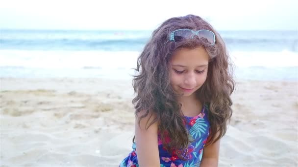 Close up of cute little girl pouring sand at the beach, slow motion