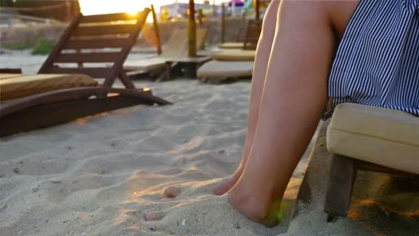 Donna / ragazza che si siede sul lettino giocando con mare spiaggia sabbia al tramonto