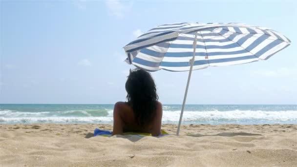 Nő a tengerparton, napozóterasz, napernyő alatt
