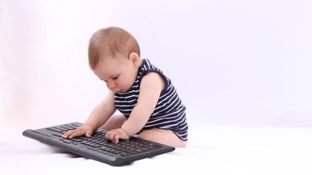 Hi Tech Baby. Boy playing with a laptop, tablet against white background