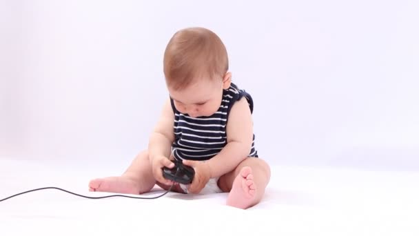 Boy playing with a laptop, tablet, mouse, keyboard against white background