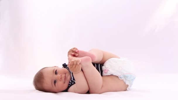 Little baby boy playing with his feet against white background