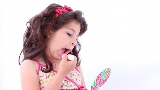 Little girl putting on a lipstick, using a lollipop as a mirror