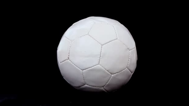 Soccer ball is deflating on a black background, close up