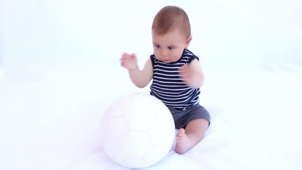 Chlapec hrát s fotbalovým míčem proti Bílému pozadí