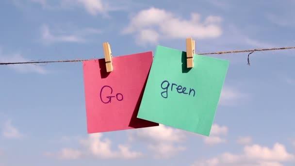 Větu Go Grren na barevný papír tlačí na laně. Pozitivní myšlení koncept