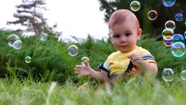 Roztomilý chlapeček se baví s mýdlové bubliny na trávě