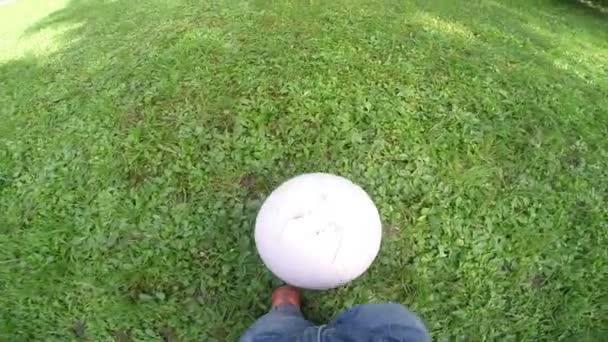 Roztomilý malý chlapec hraje s fotbalovým míčem, podporuje jeho matka