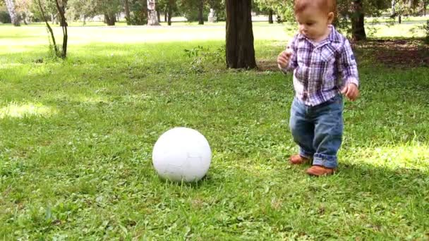 Cute little boy playing with soccer ball supported by his mother