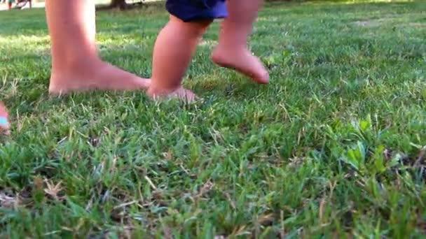 Roztomilý chlapeček, takže jeho první kroky na trávě podporující jeho matka