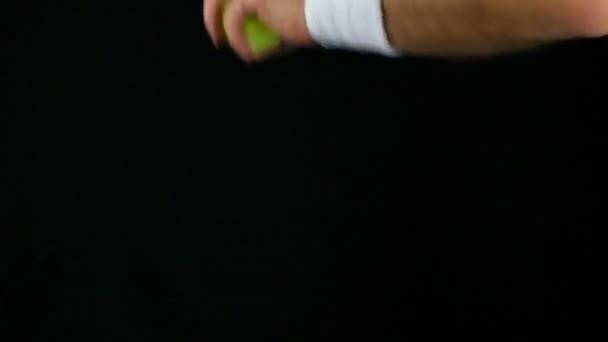 Zpomalený pohyb tenista, připravuje se trefit míč s jeho raketa, černé pozadí
