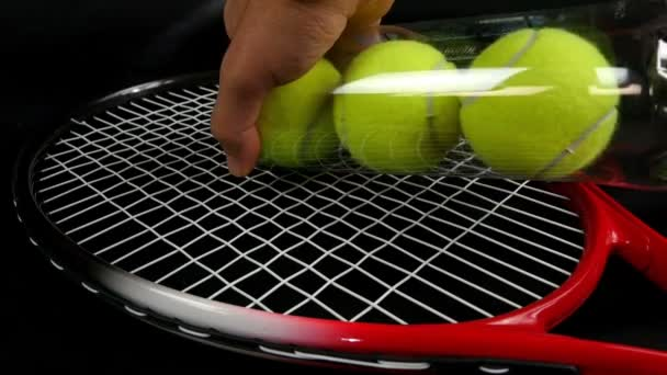 Rukou dávat sérii tří nových tenisových míčků přes tenisovou raketu na černém pozadí