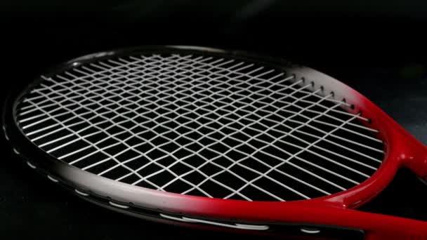 Rukou dávat dva tenisové míčky přes tenisovou raketu na černém pozadí