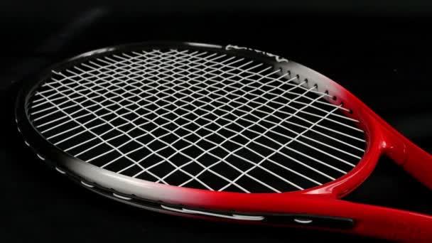 Velká Británie, Londýn - 10. května 2015: Head tenisový míč skákací nad tenisovou raketu na černém pozadí