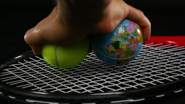 Rukou dá jeden tenisový míček a jedna kulička s zeměkoule na tenisovou raketu na černém pozadí