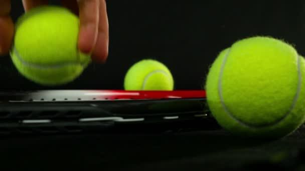 Ruky vloží jeden tenisový míček nad tenisovou raketu, černé pozadí