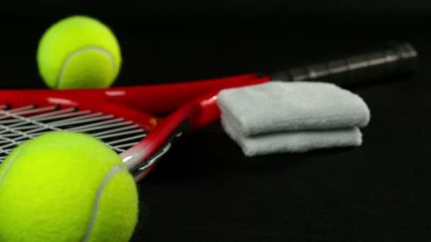 Tenisové vybavení - tenisové rakety se třemi tenisovými míčky na něm na černém pozadí, dolly