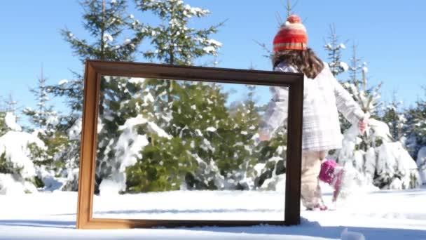 Matka a dcera hrají v zimním sněhu, rámu v popředí. Obraz v rámečku je s efektem olejnatých barev