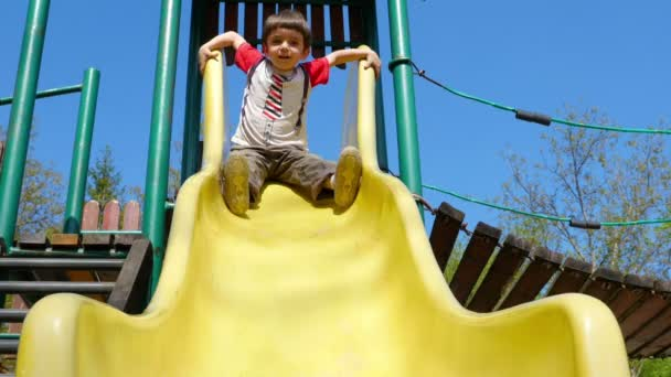 A little boy playing on a slide in a playground. Recreation outdoors for kids
