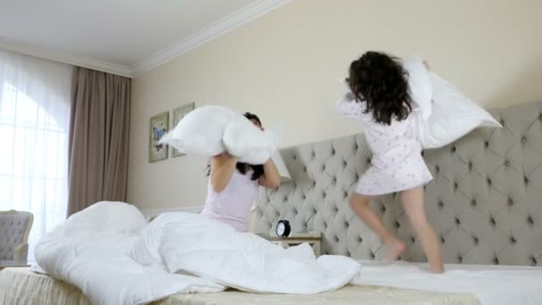 Mother and daughter having pillow fight in the bedroom