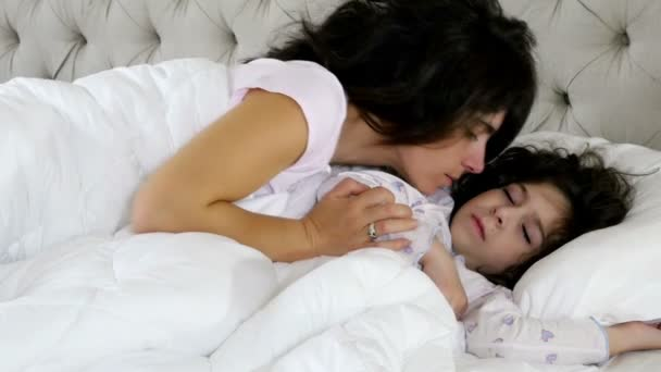 Mother kissing her little daughter while she is sleeping in bed