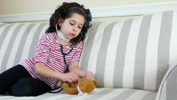 Little girl with sore throat examining her ill bear toy with a stethoscope