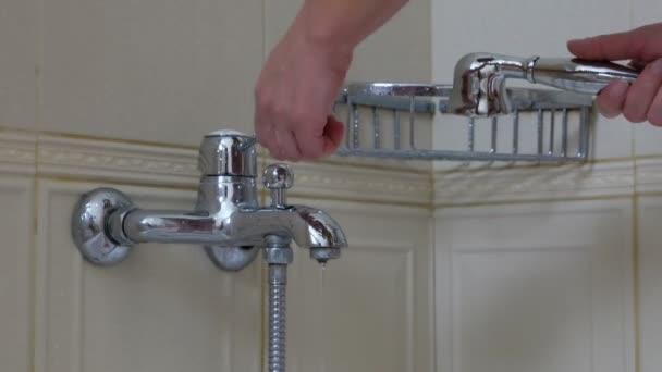 Ženská ruka vede vodu z kohoutku vana v koupelně