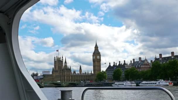 4k pohled na Big Ben a domy parlamentu z pohybující se lodi na řece Temži, Londýn