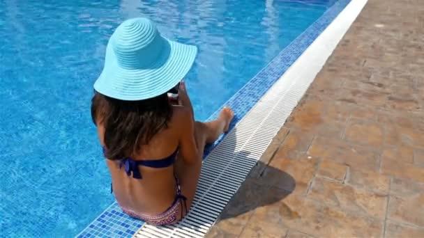 junge Frau in Badeanzug und blauem Hut, die am Rande eines Swimmingpools sitzt und sich sonnt