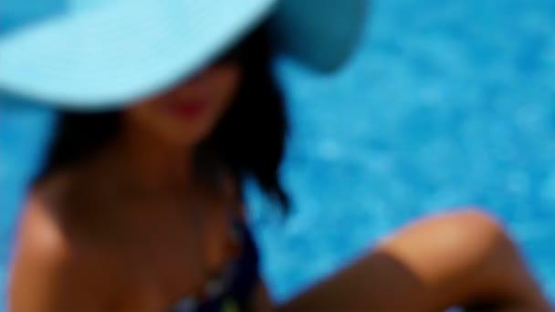 Mladá žena v plavání oblek a modrý klobouk sedí na kraji bazénu a přijímání fotografií ze sebe s mobil