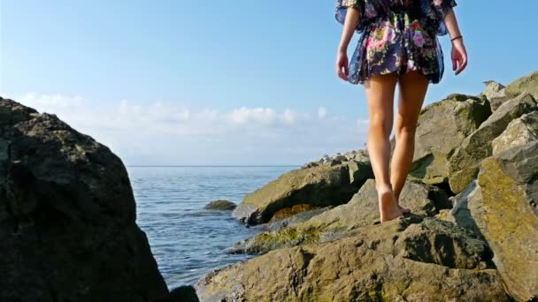 Fiatal nő nyári ruha és a kék sapka ült a sziklák, a tenger partján