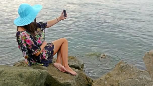 Young woman in a summer dress and blue hat sitting on the rocky sea shore and taking photo of herself with cellphone