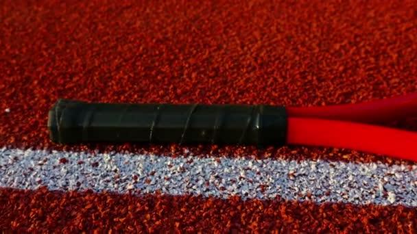 Tenisovou raketu a tři míčky ležící na červené tenisový kurt, dolly