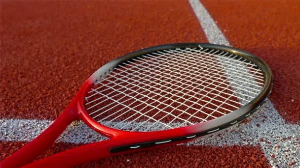 Tenisová raketa leží na červené tenisový kurt, ruka umístí tři tenisové míčky